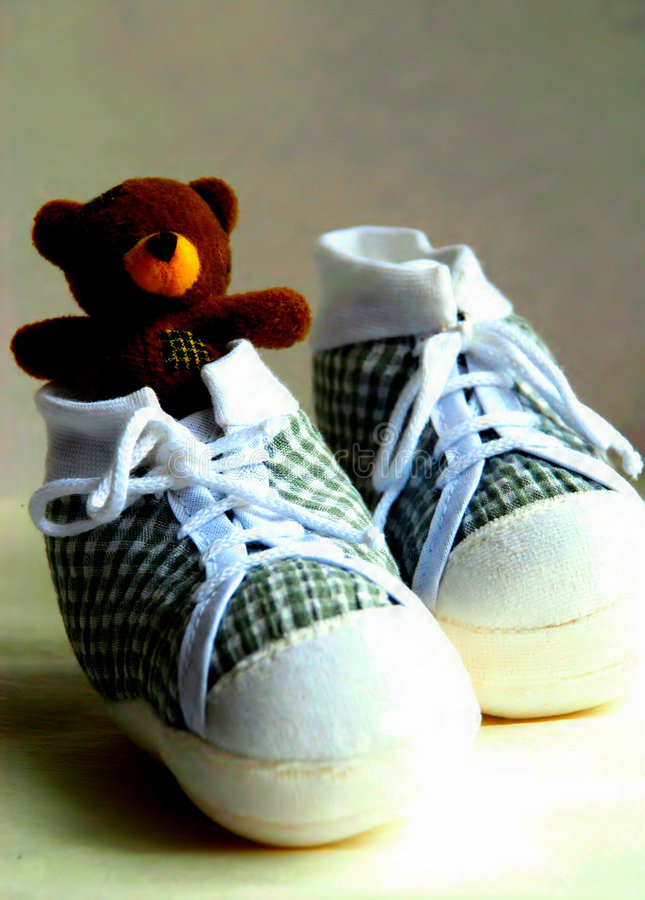 Teddy bear in baby's shoes royalty free stock images