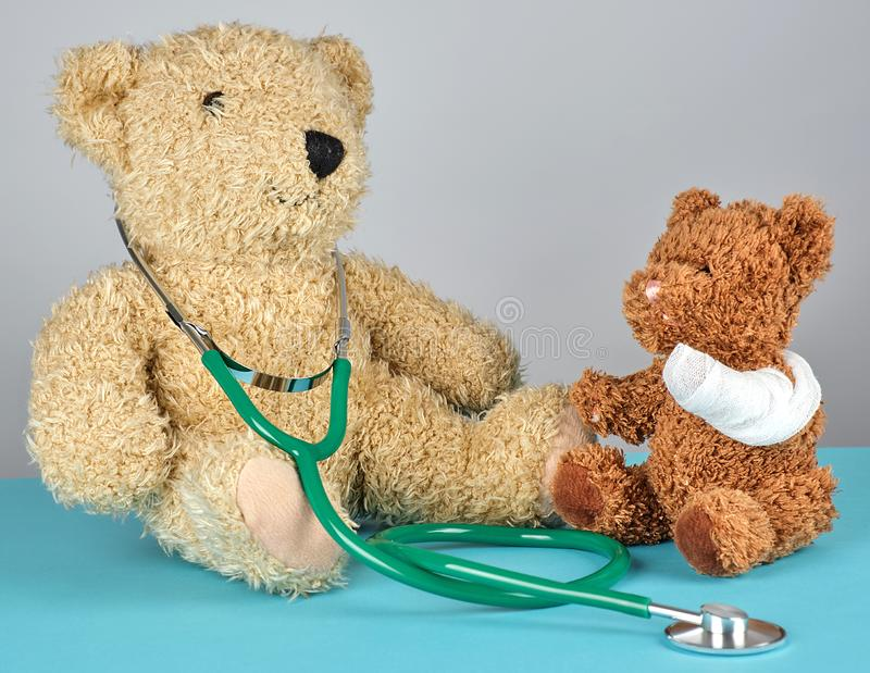 Teddy bear with bandaged paw and stethoscope. Pediatrics concept stock images