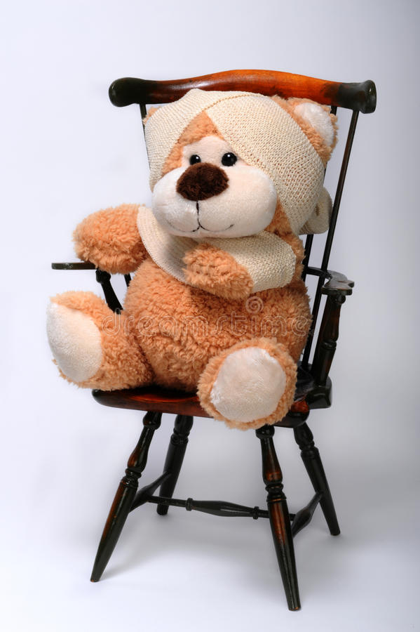 Teddy bear in bandages. Large teddy bear in bandages on chair, white studio background stock photo