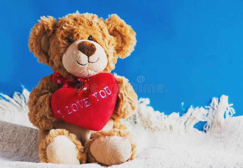 Teddy bear and big red heart with text I Love You isolated stock images