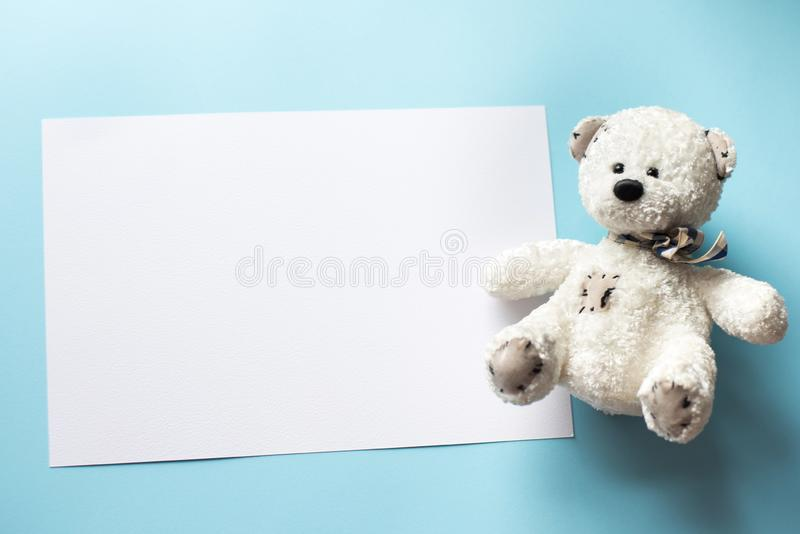Teddy bear child toy with frame for photo or gift card on a pastel blue background stock photography
