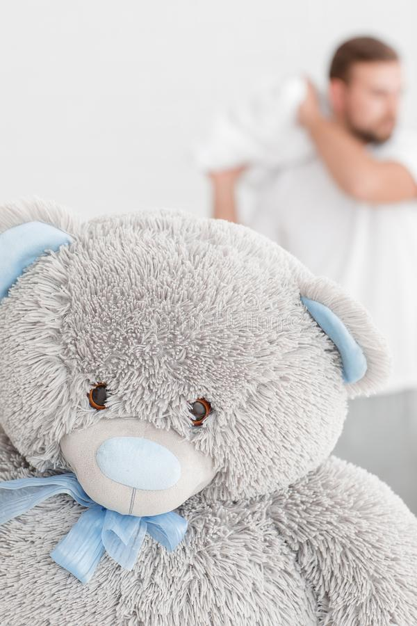 The teddy bear is close-up. On the blurry background is a man. stock image