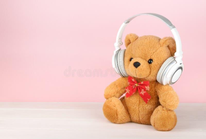Teddy Bear com os fones de ouvido com espaço da cópia fotografia de stock royalty free