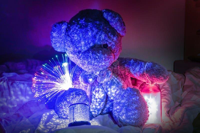 Teddy Bear con las luces y la estrella ornamentales se enciende en cama imagen de archivo