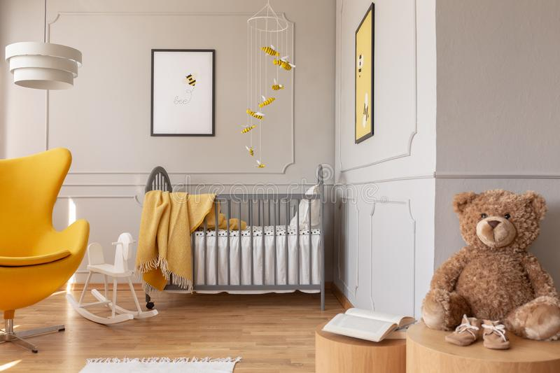Teddy bear, crib and yellow armchair in a toddler room interior. Real photo stock photo
