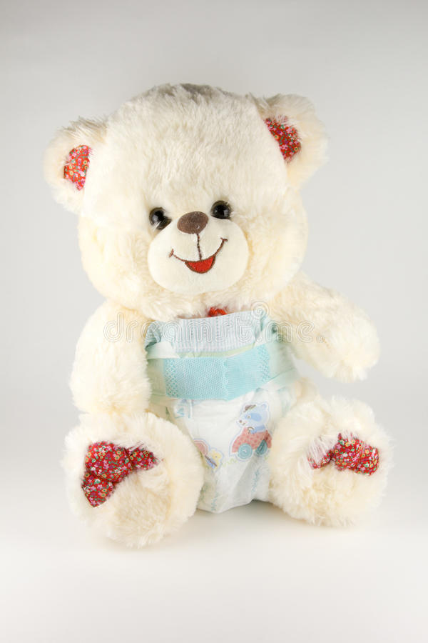 Teddy bear in a diaper on a white background.  royalty free stock image