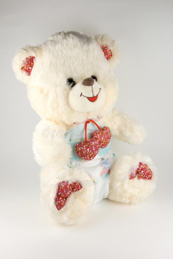 Teddy bear in a diaper on a white background.  stock photos