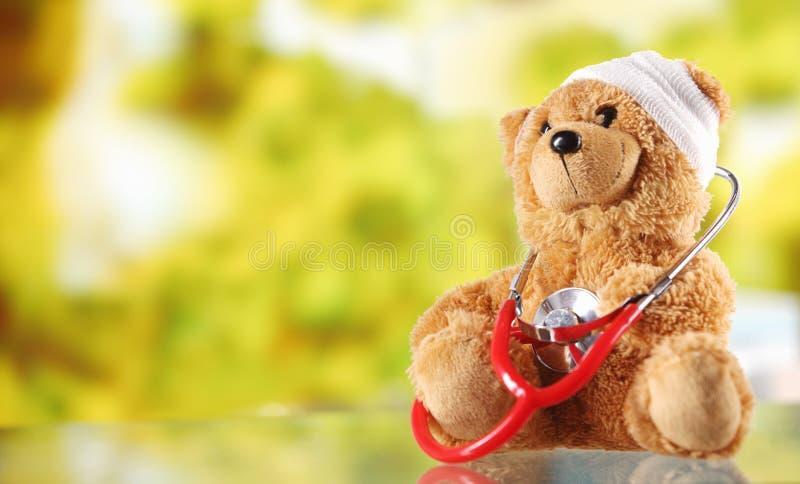 Teddy Bear doente com o estetoscópio na tabela de vidro imagens de stock