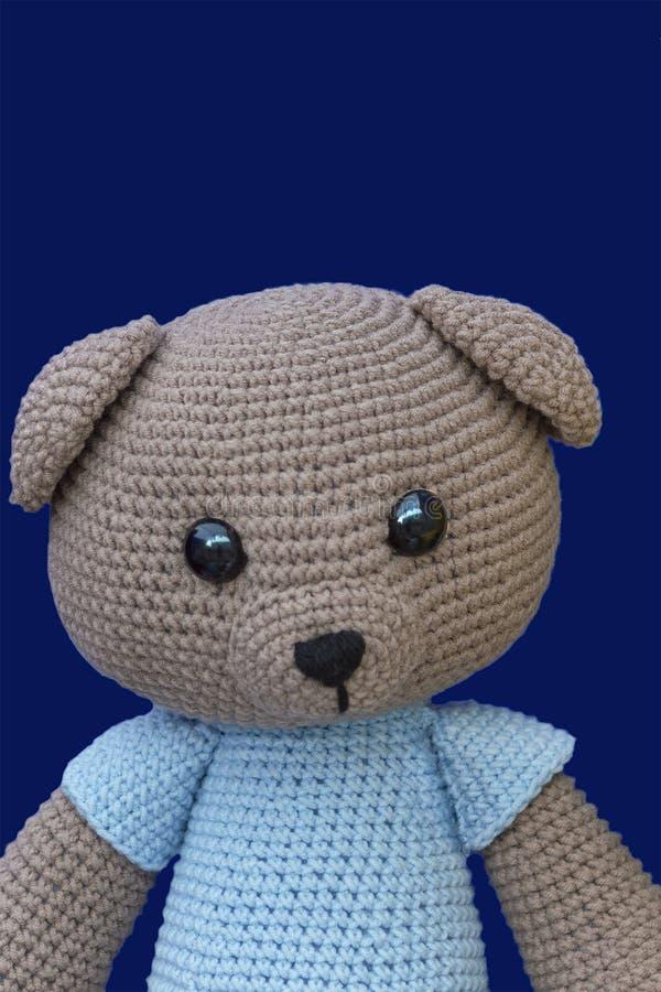 Teddy bear doll on a blue background at the fair stock photos