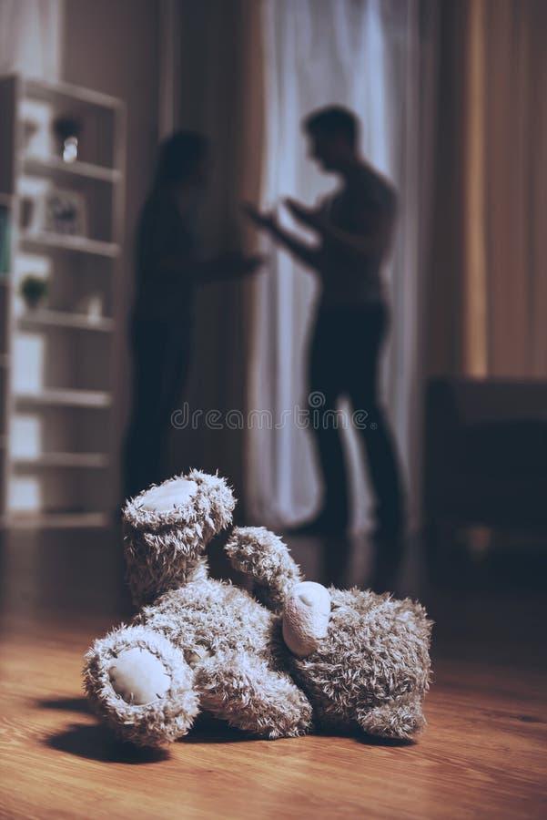 Teddy Bear en piso y padres en conflicto foto de archivo