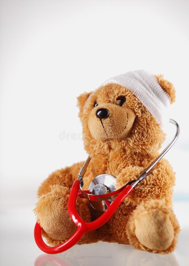 Teddy Bear enfermo conceptual con el dispositivo del estetoscopio imagenes de archivo