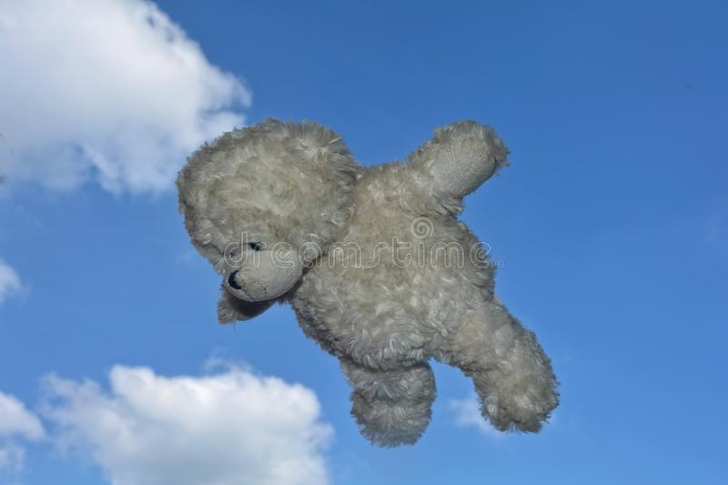 Teddy bear flies in the air with blue sky with clouds stock image