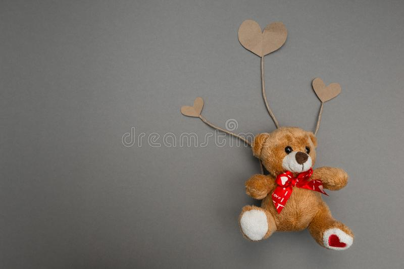 Teddy bear flies on paper hearts as on the balls stock photo