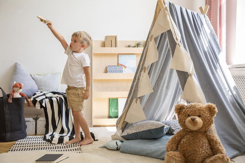 Teddy bear on the floor of stylish single child playroom with tent and toys, real photo stock photo