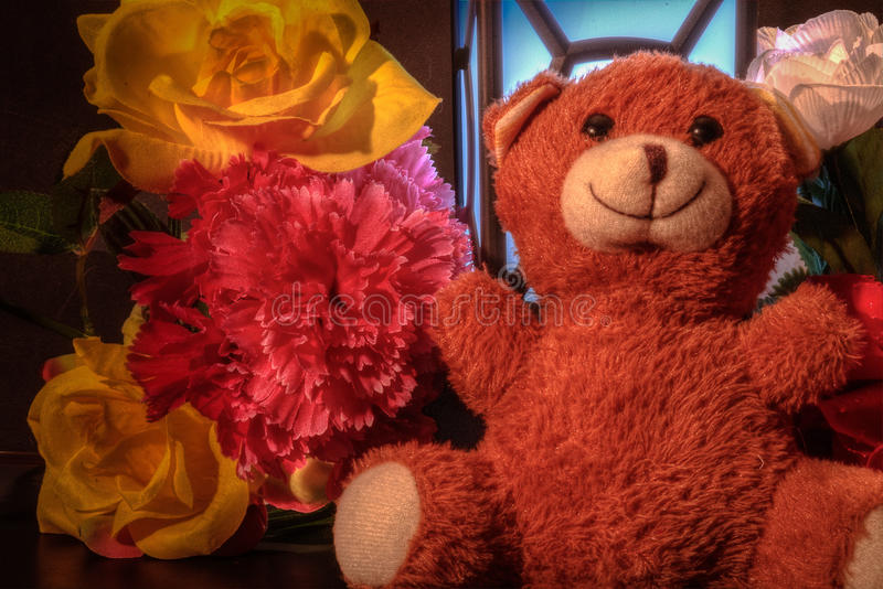 Teddy bear with flowers and light. stock image