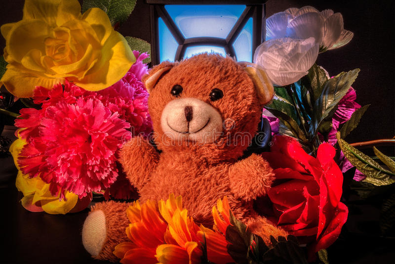 Teddy bear with flowers and light. royalty free stock photo