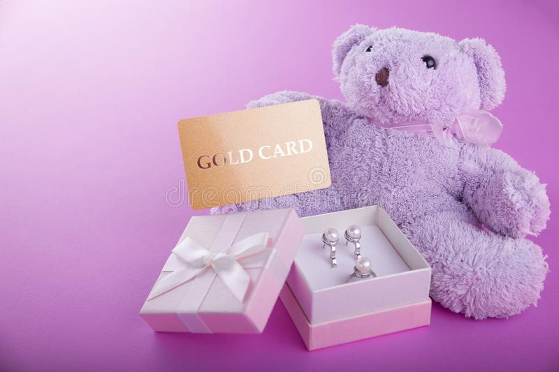 Teddy bear with a gift box for Valentines day on purple background stock photos