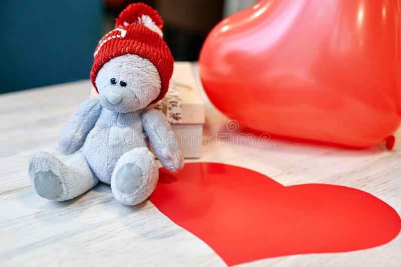 Teddy bear and gift box on a wooden table in Valentine`s Day. Teddy bear in red cap and gift box on a wooden table in Valentine`s Day. Balloon and card in the stock photography
