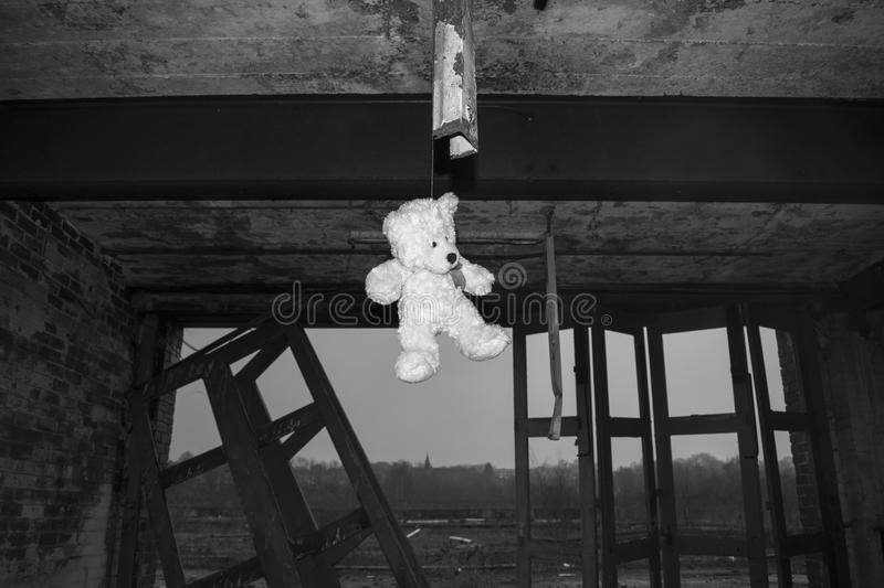 Teddy Bear Hanging In Derelict Verlaten Fie Station Building In Black & Wit royalty-vrije stock fotografie