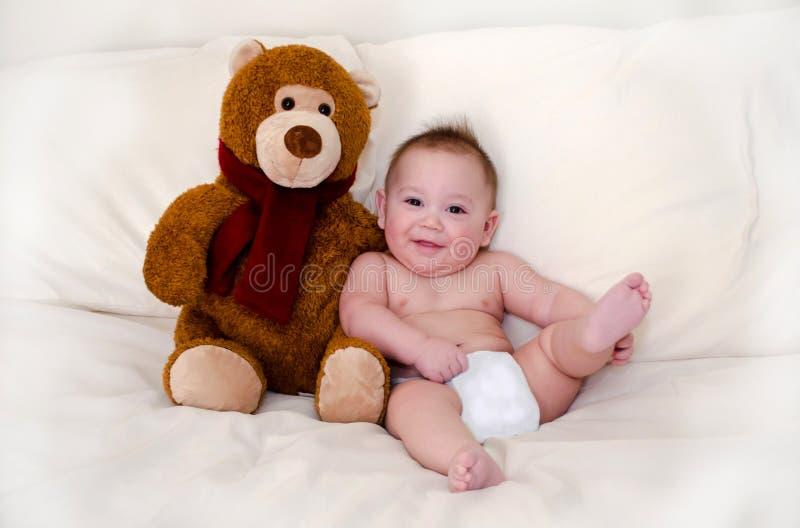 Teddy bear and happy baby boy stock photos