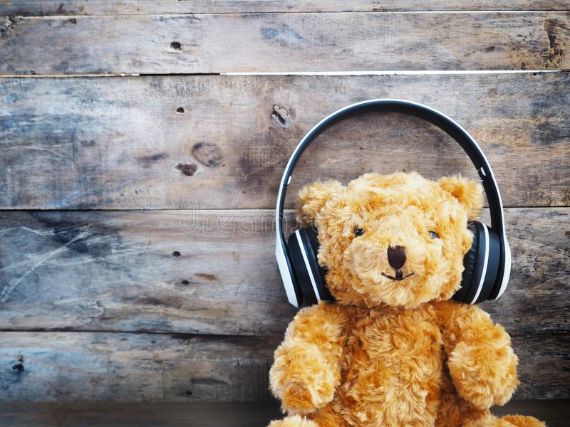Teddy bear in headphone over old wood wall background stock photo