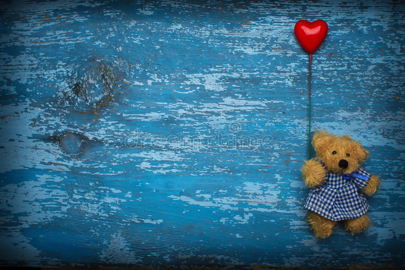 Teddy bear with heart baloon. Teddy bear holding red heart baloon on wooden background. Free space for your text stock photos