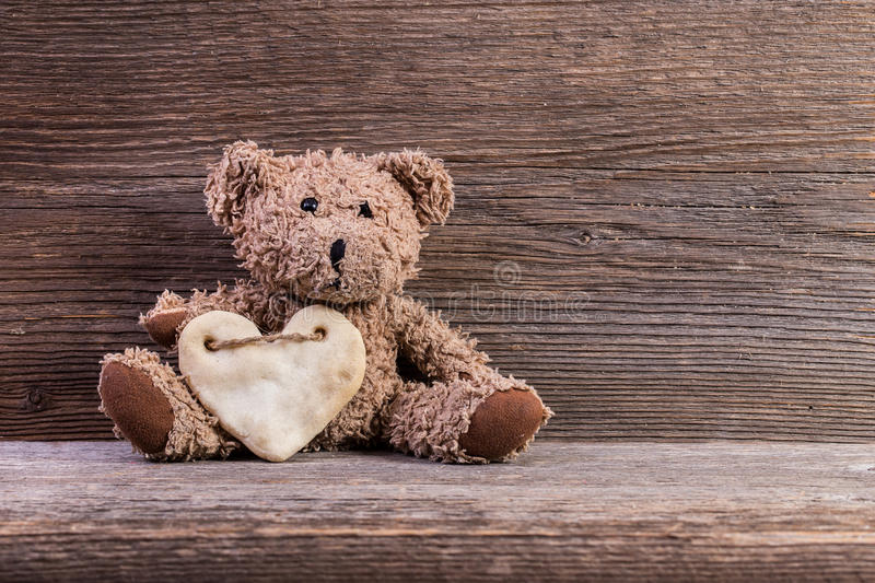 Teddy bear with heart sitting on old wood background. Teddy bear with heart sitting on old wood background stock photo