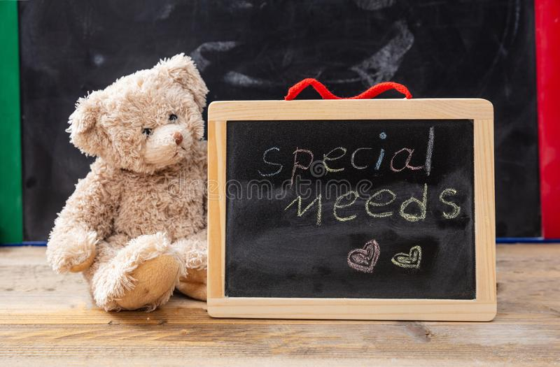 Teddy bear hiding behind a blackboard. Special needs text drawing on the blackboard stock images