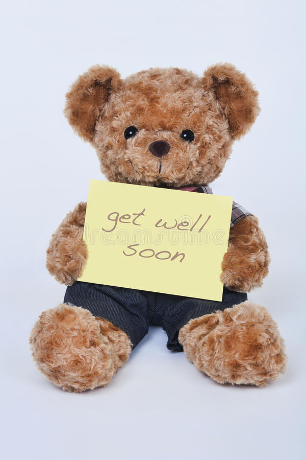 Teddy bear holding a yellow sign saying Get Well Soon isolated on white background. A cute teddy bear holding a yellow sign saying Get Well Soon isolated on a royalty free stock images