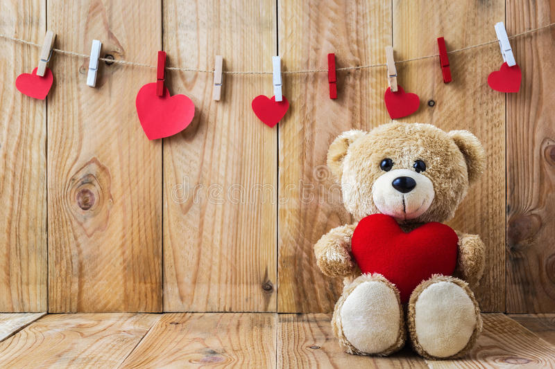 Teddy bear holding a heart-shaped pillow stock photography