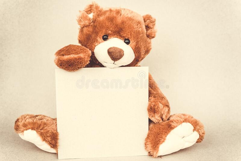 Teddy bear holding a place for text from craft cartoon paper. Vintage retro romantic style. Tempate royalty free stock photo