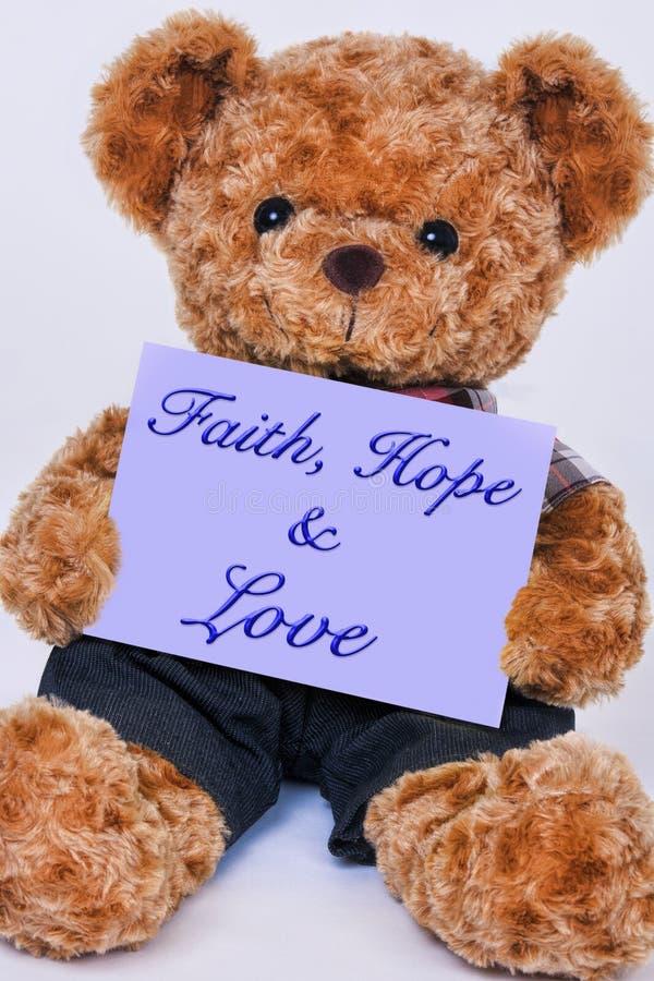 Teddy bear holding a purple sign that says Faith, Hope and Love stock image