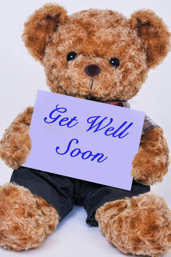 Teddy bear holding a purple sign that says Get Well Soon. Cute teddy bear holding a purple sign that reads Get Well Soon isolated on a white background stock photography