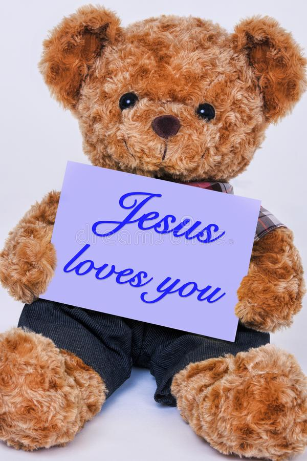 Teddy bear holding a purple sign that says Jesus loves you. Cute teddy bear holding a purple sign that reads Jesus loves you on a white background royalty free stock photo