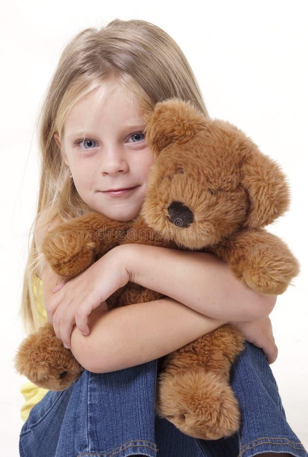 Teddy Bear Hug. Girl with shy expression with her teddy bear in a tigh hug stock image