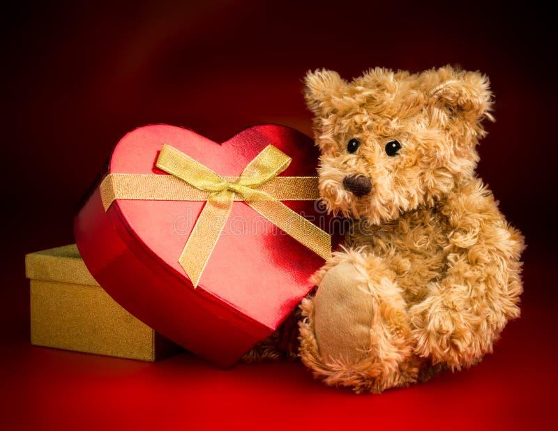 Teddy Bear Hugging uma caixa dada forma coração fotos de stock
