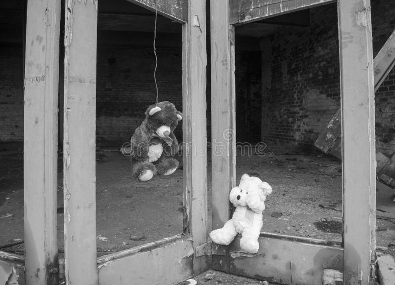 Teddy Bear Hung On Doors Of Derelict Abandoned Fie Station Building With Other Bear Crying In Black & White. Teddy Bear Hung On Doors Of Abandoned Fie Station stock images