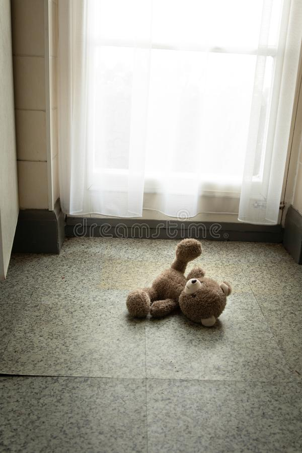 Teddy bear left behind on the floor in the kitchen royalty free stock photos