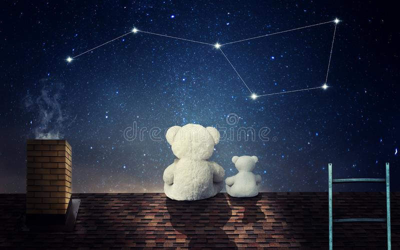A teddy bear with a little bear sits at night on the roof of the house and looks at the constellation of the big bear. royalty free stock image