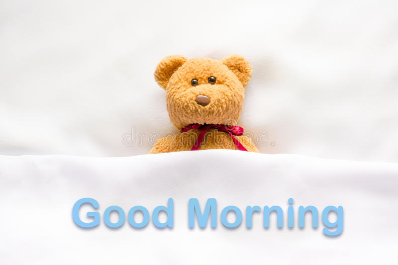 Teddy Bear lying in the white bed with message ' Good morning '.  royalty free stock photo