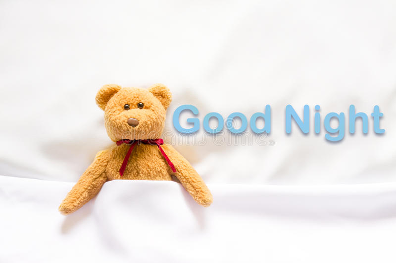 Teddy Bear lying in the white bed with message ' Good night '.  royalty free stock photos