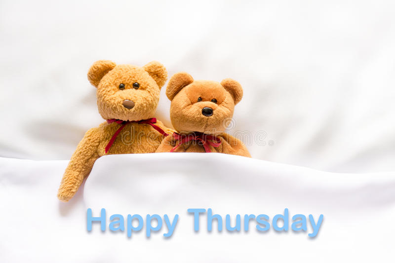 Teddy Bear lying in the white bed with message Happy Thursday stock photos