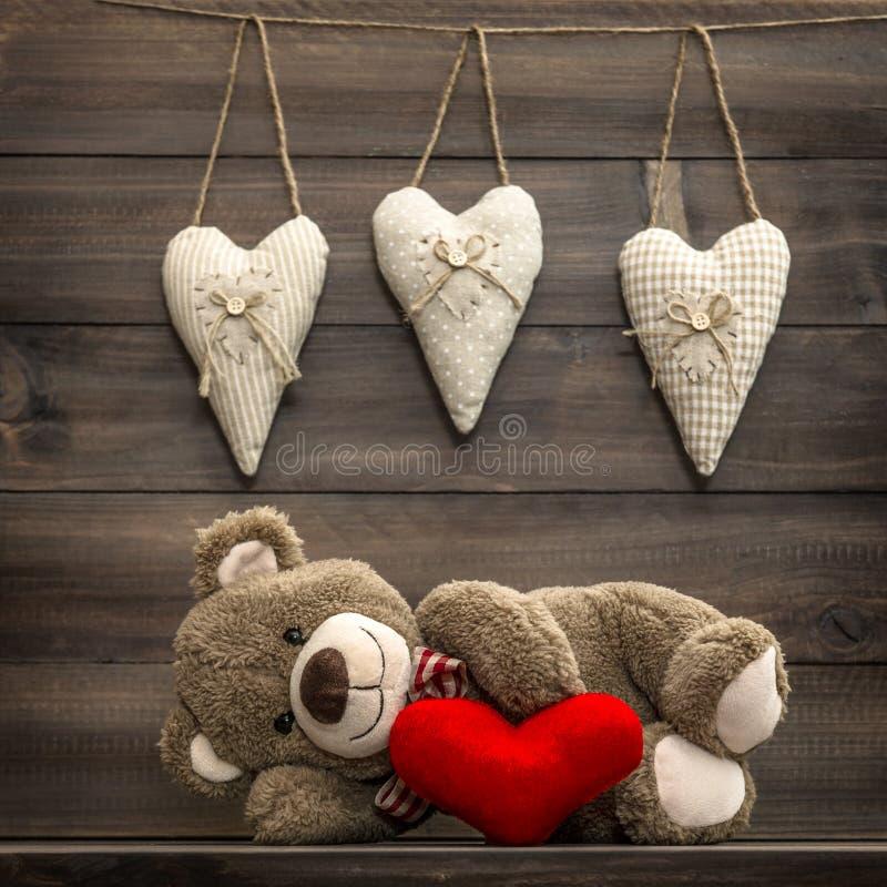 Teddy Bear med den röda hjärtakudden red steg arkivfoton