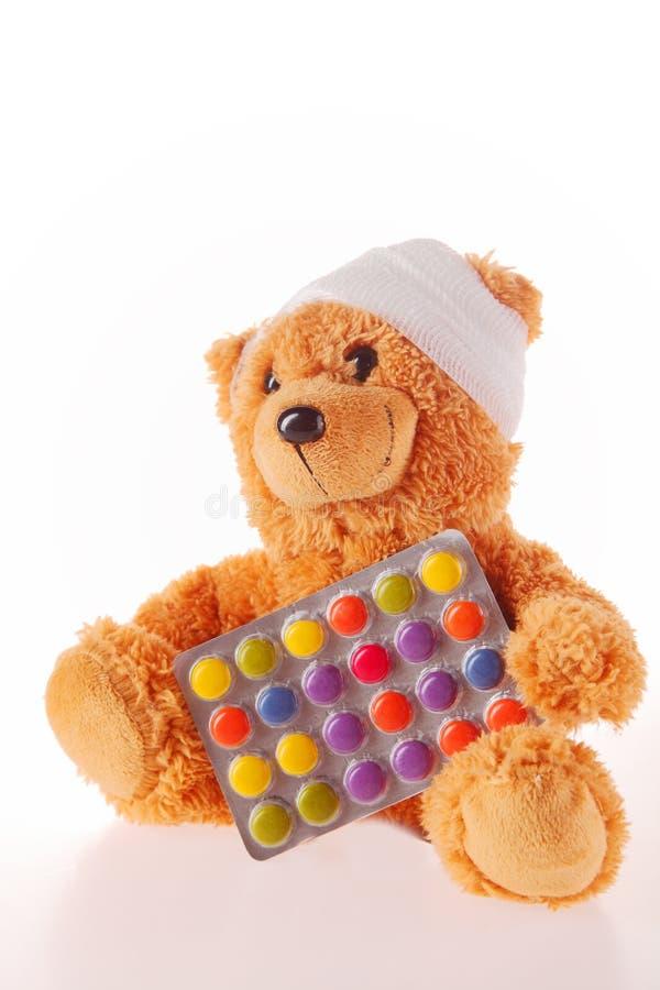 Teddy Bear met Verbandholding Gekleurde Pillen stock fotografie