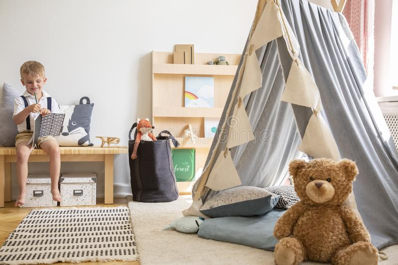 Teddy bear next to grey scandinavian tent in stylish boy`s bedroom with furniture made from natural materials, real photo with royalty free stock image