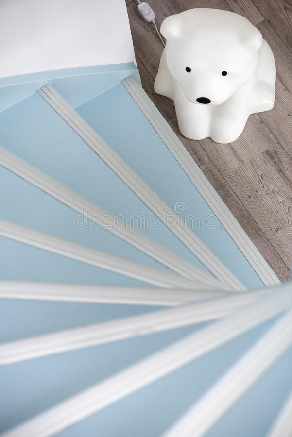 Teddy bear night lamps at the bottom of a circular light blue staircase. Top view stock photography