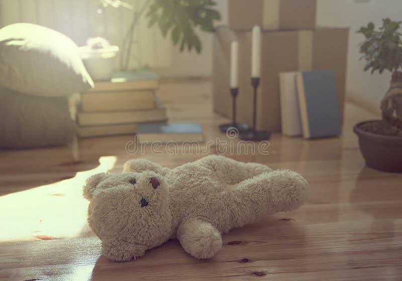 Teddy Bear no assoalho e as caixas, os materiais e as plantas móveis na casa nova imagens de stock