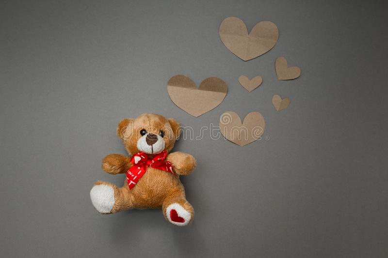 Teddy bear and paper hearts stock image