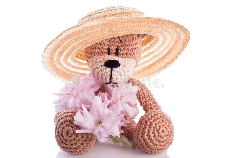 Teddy bear with pink blossom. Brown stuffed animal teddy bear with pink blossom stock photography