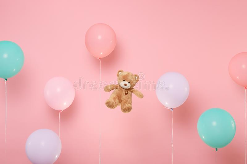 Teddy bear plush toy on pastel bright trending pink background with colorful air balloons. Decoration for birthday stock image